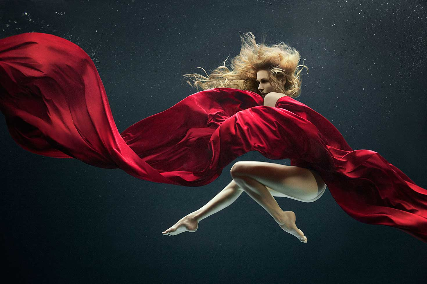 Nude blond mermaid styled model dances within a black water space with flowing red silk fabric. Copyright 2016 - Zena Holloway