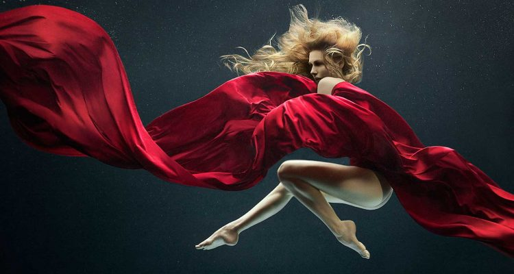 Nude blond mermaid styled model dances within a black water space with flowing red silk fabric