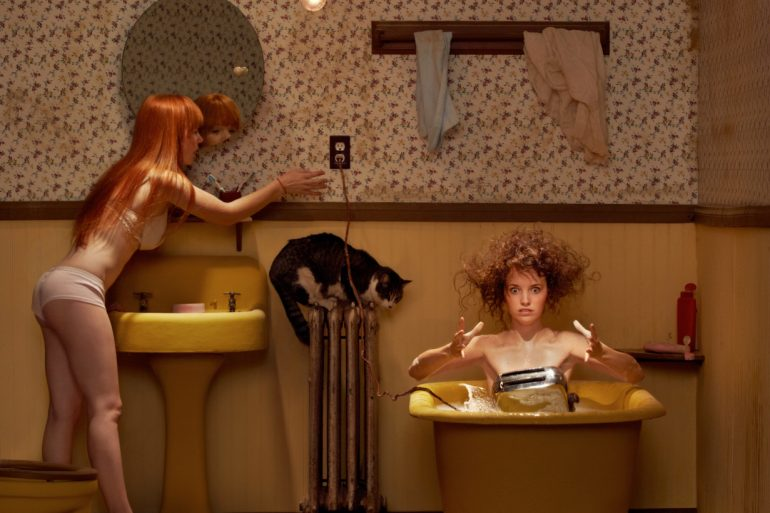 Two women appear in a square cropped, stylised image. One woman stands at the bathroom sink whilst another appears in the bathtub who has accidentally dropped a toaster into the water and she is surprised and shocked at her mistake.