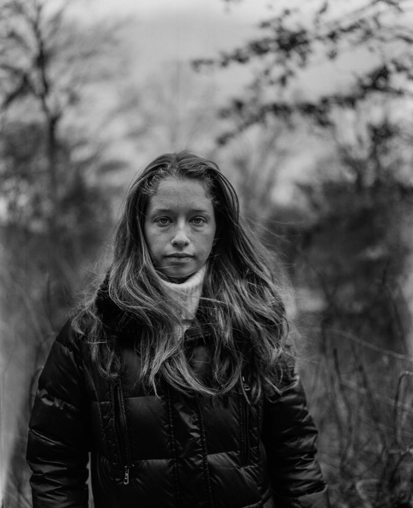 A black and white image of a girl in a jacket, long hair and staring at the camera without smiling. Photograph by Roshni Khatri.