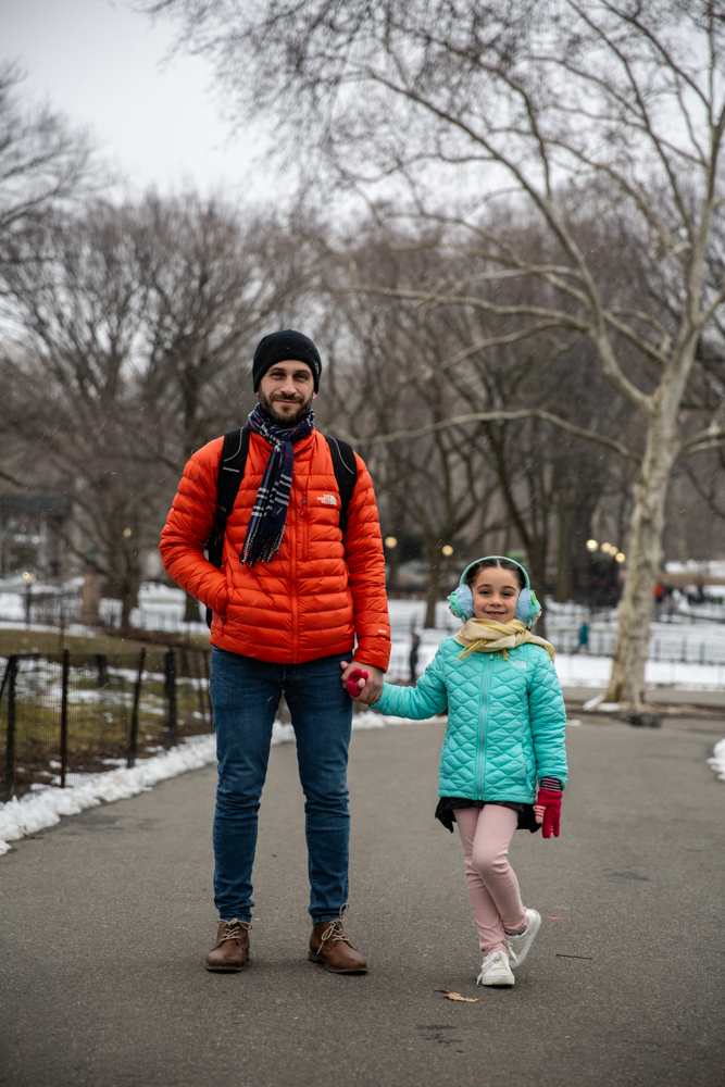 A man in a bright orange jacket stands in a city park, snow in the background and leafless trees. He holds the hand of a little girl with bright blue earmuffs and pink trousers. Both are staring at the camera. Photograph by Roshni Khatri.
