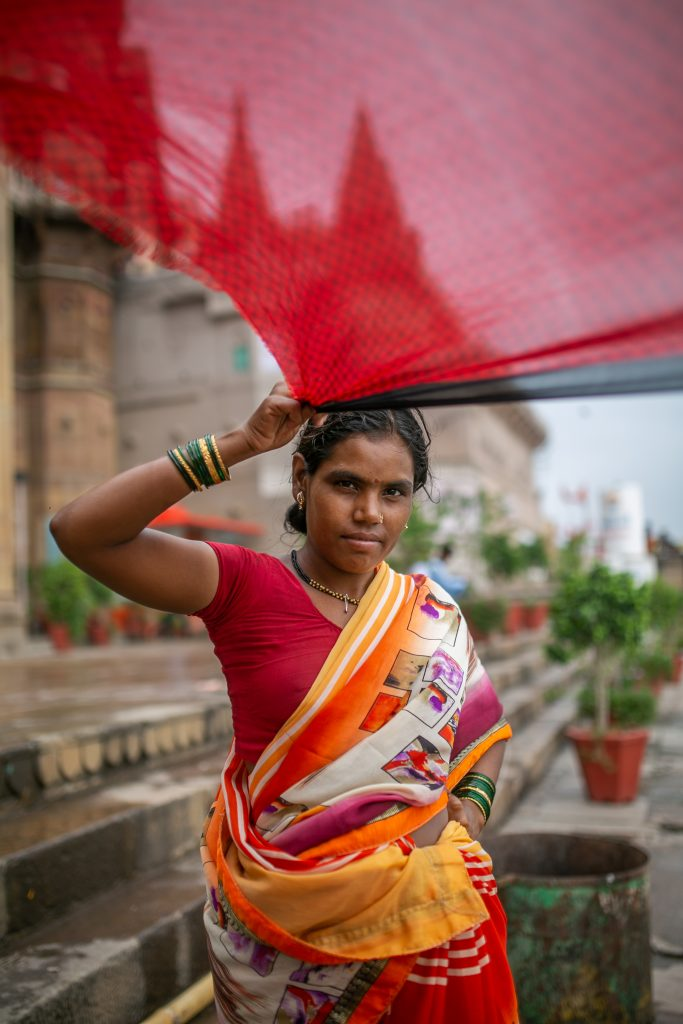 An Indian woman stands on steps in front of large buildings and holds a large piece of red cloth above her head. She is wearing what looks to be traditional clothing.