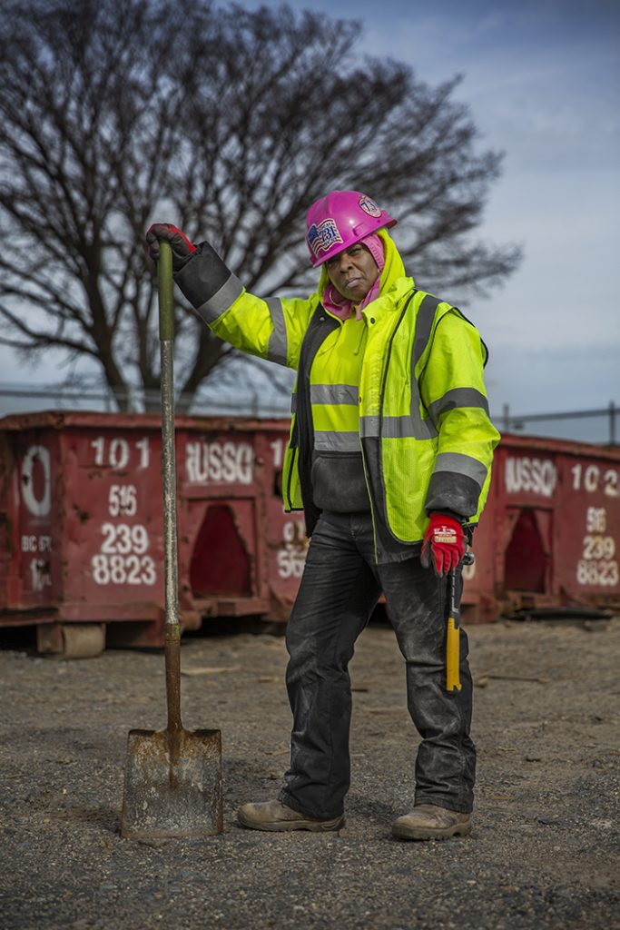 A woman with a pink hard-hat, fluoro vest and dark work boots stands on a construction site holding a shovel.
